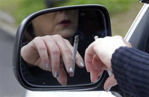FILE - In this Saturday, March 2, file 2013 photo, a woman smokes a cigarette while sitting in her truck in Hayneville, Ala. The federal health care law requires insurers to accept all applicants regardless of pre-existing medical problems. But it also allows them to charge smokers premiums that are up to 50 percent higher than those offered non-smokers - a way for insurers to ward off bad risks. (AP Photo/Dave Martin)