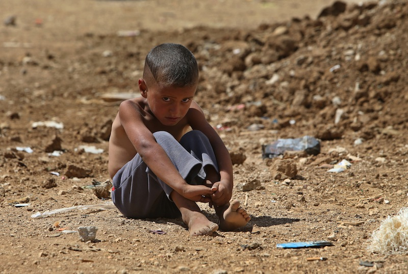A Syrian refugee sits on the ground at a temporary refugee camp in the eastern Lebanese Town of Al-Faour, Bekaa valley near the border with Syria, on Wednesday, Sept. 11, 2013. Lebanon is a tiny country that shares a porous border with Syria, and has seen cross-border shelling, sectarian clashes and car bombings in recent months related to the civil war raging next door. Key international players were moving on two diplomatic fronts Wednesday, Sept. 11, 2013 to try to put Syria's chemical weapons under international control, and a fresh effort appeared to be underway to get the government and opposition to peace talks. (AP Photo/Hussein Malla)