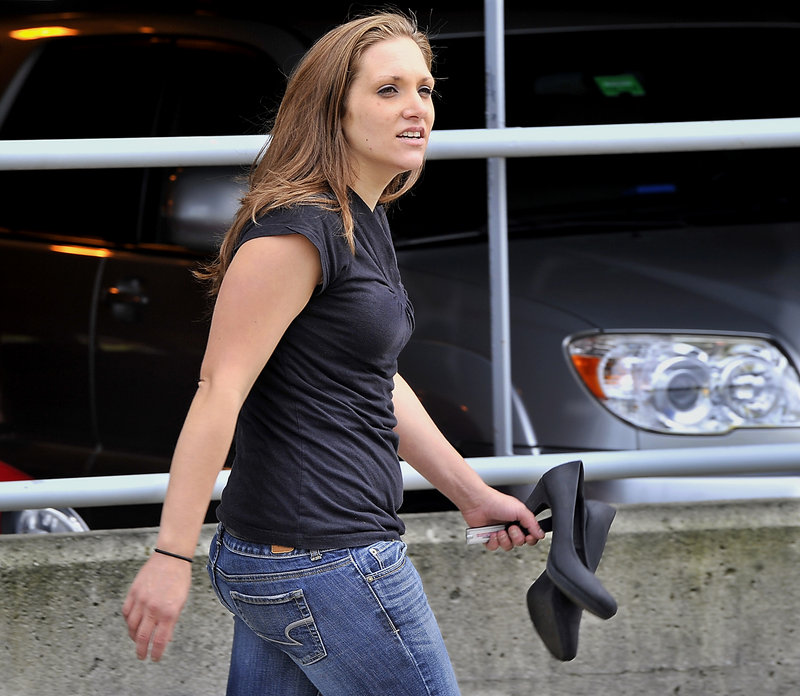 Trista Reynolds holds her high heeled shoes as she comes back from chasing Justin DiPietro and accusing him of killing Ayla Reynolds outside the Cumberland County Courthouse on Wednesday, Sept. 25, 2013.