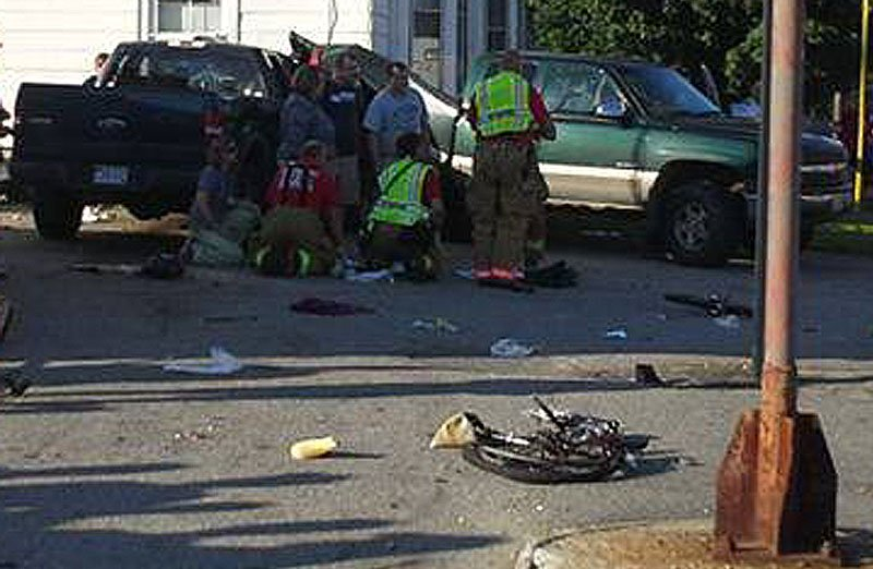 In this Aug. 2 file photo, rescuers attend to one of the victims at the scene of the crash in Biddeford where an alleged drunken driver hit a family of bicyclists. A civil lawsuit may be filed on behalf of the mother and toddler who survived their injuries after a pickup truck hit them and the toddler's father last month. The father died of his injuries.