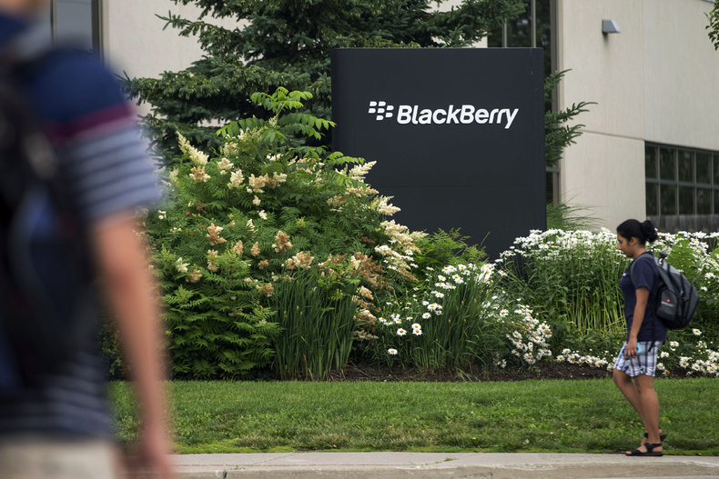 Pedestrians walk near BlackBerry's headquarters in Waterloo, Ontario, in July. BlackBerry said Friday that it will lay off 4,500 employees, or 40 percent of its global workforce and is announcing a nearly $1 billion second-quarter loss in a surprise early release of earnings.