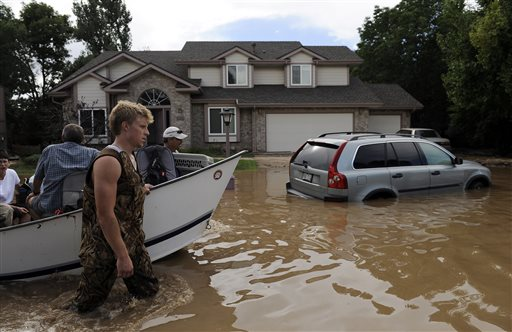 Eric and Pat Machmuller lead a boat down a residential street Saturday to help residents gather pets and belongings from their flooded homes in Longmont, Colo.