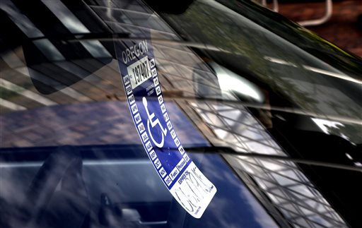 A handicapped parking tag hangs from the rearview mirror of a car parked at a metered parking spot in Portland, Ore., where it's common to find blocks in which there are more cars with placards than without.