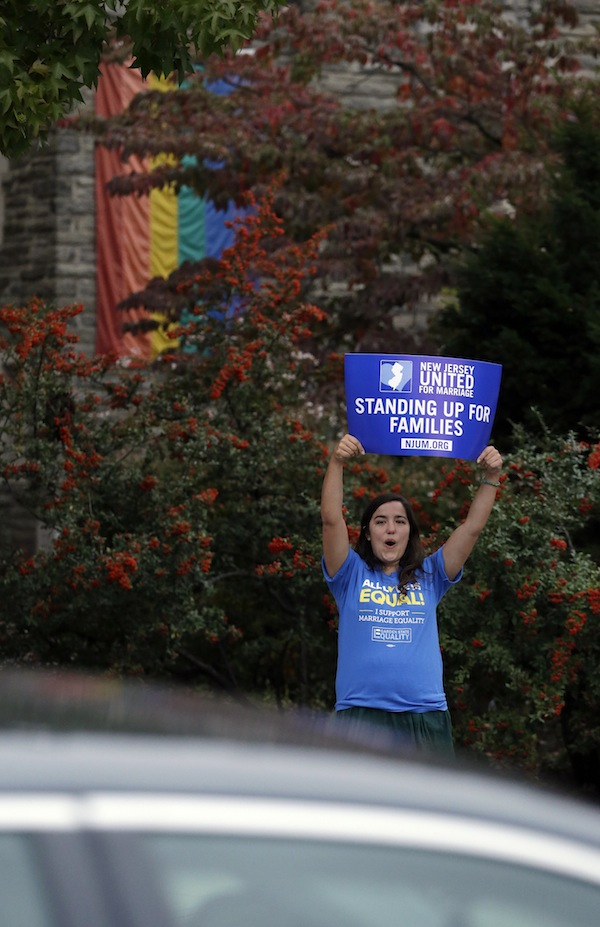Alex Nikazmerad, 24, of North Plainfield, N.J., shouts at a passing vehicle before a rally hosted by Garden State Equality in Montclair, N.J., hours after same-sex marriages were made legal as of Oct. 21 by a state judge on Friday.