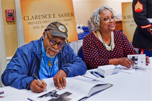 Clarence E. Sasser signs autographs alongside his girlfriend, Patricia Washington. Private First Class Sasser served in Vietnam as a combat medic.