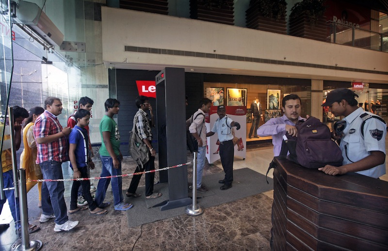 In this Tuesday, Sept. 24, 2013 photo, shoppers walk through a metal detector before they are frisked by a private security guard as another security guard, right, checks a bag at the entrance to a shopping mall in New Delhi, India. Shopping centers across the globe are adding guards and increasing security following the attack in Nairobi over the weekend. (AP Photo/Manish Swarup)