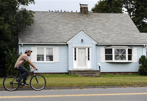 A man rides a bicycle by a house owned by the uncle of former New England Patriots' tight end Aaron Hernandez, in Bristol, Conn. A group of people who all have ties to the small cape-style home have become central figures in the investigations linking former New England Patriot Hernandez to two murder cases.