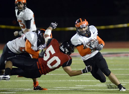 Mansfield's Jonathan Keller (50) attempts to block Princeton's Kevin Ma, right, on Saturday. The game marks the first time that Mansfield has held an official night football game since 1892 when Mansfield staged the first-ever night football game.