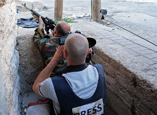 In this Wednesday, Sept. 11, 2013, photo released by the Syrian official news agency SANA, a journalist records a Syrian government soldier as he aims his weapon, during clashes with Free Syrian Army fighters in Maaloula village, northeast of Damascus, Syria.