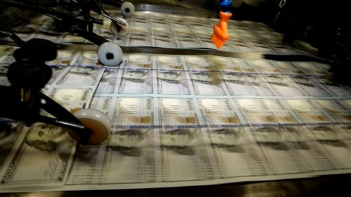 Sheets of uncut $100s run through a printing press at the Bureau of Engraving and Printing Western Currency Facility in Fort Worth, Texas.