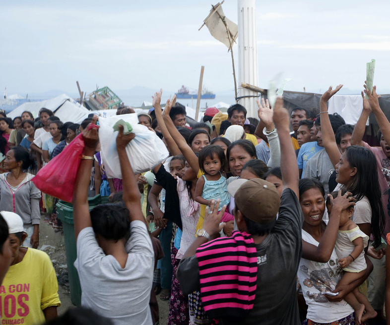 Villagers who fled the fighting between government forces and Muslim rebels cheer a fellow evacuee who just got her bag of relief supplies Wednesday in Zamboanga city in southern Philippines.