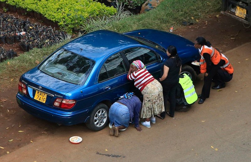 People take cover behind a car along a road during heavy gunfire at Westgate shopping centre in Nairobi September 23, 2013. A day after a Twitter post linked Maine to Saturday's terrorist attack in a mall in Nairobi, Kenya, law enforcement officials refused to say whether they are investigating the possibility that radical Islamist groups are trying to recruit new members in the state. (REUTERS/Noor Khamis) :rel:d:bm:GM1E99N1S4001