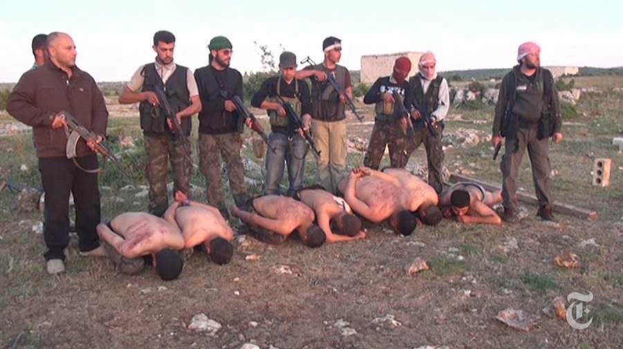 In this screen capture from a video on the New York Times website that was posted on Thursday, Syrian rebel fighters stand over seven Syrian government soldiers with guns near Idlib, Syria in April 2012. The rebel fighters, under orders from commander Abdul Samad Issa, at right, allegedly shot the captured soldiers and put their bodies into a mass grave.