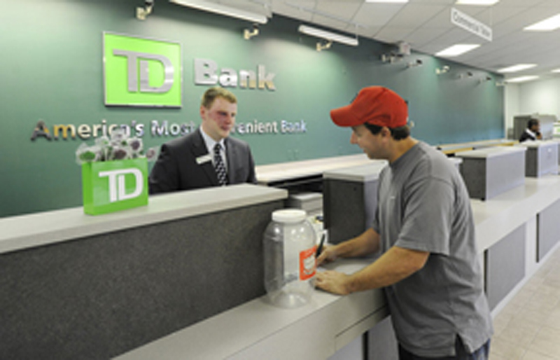 A TD Bank customer service representative helps a new customer Matthew Hodgins open an account. Some TD Bank customers in New Hampshire and Vermont got other people's financial information with their own bank statements.