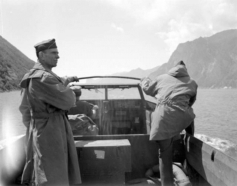 In this historic image, Gen.George P. Hays, left, leads an American amphibious vehicle as it crosses an Italian lake during World War II.