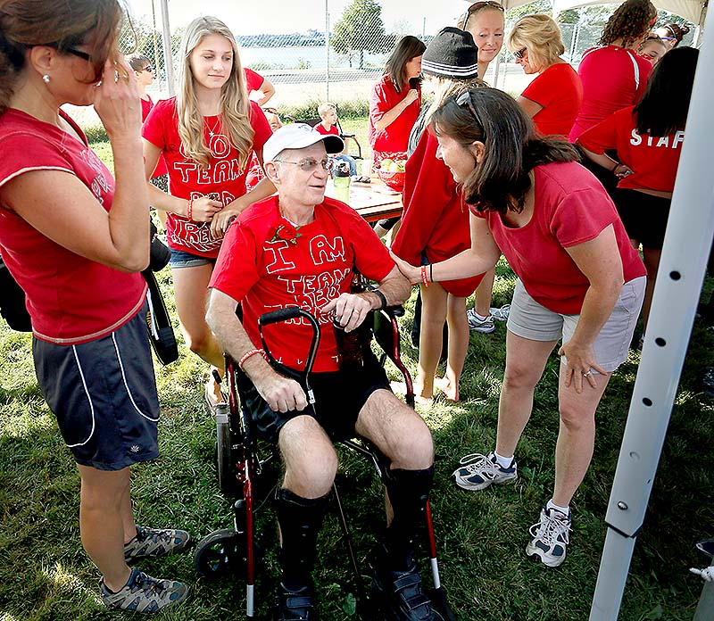 Jim Caldwell of Falmouth visits with friends and family before the start of the Walk to Defeat ALS in Portland on Saturday. Behind Caldwell is his daughter Sarah, 16.