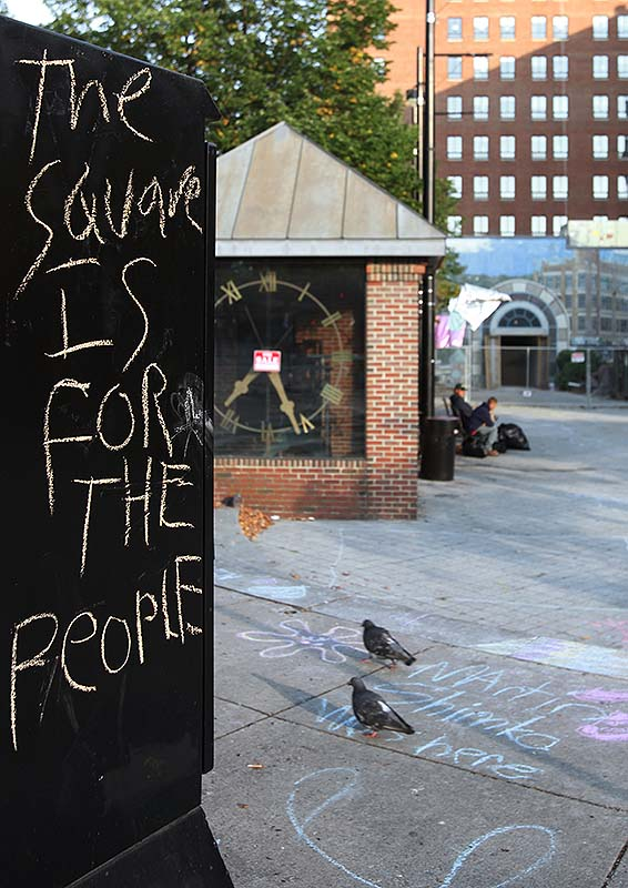 A message written in chalk protesting the sale of part of Congress Square Plaza.