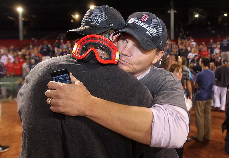 Boston Red Sox GM Ben Cherington, right, is embraced by one of his players after the Red Sox clinched the AL East title with a 6-3 win over the Toronto Blue Jays in a baseball game at Fenway Park on Friday night.