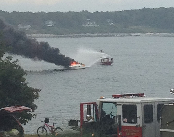 A boat burns in Portland Harbor on Sunday afternoon. Four people and a dog were rescued.