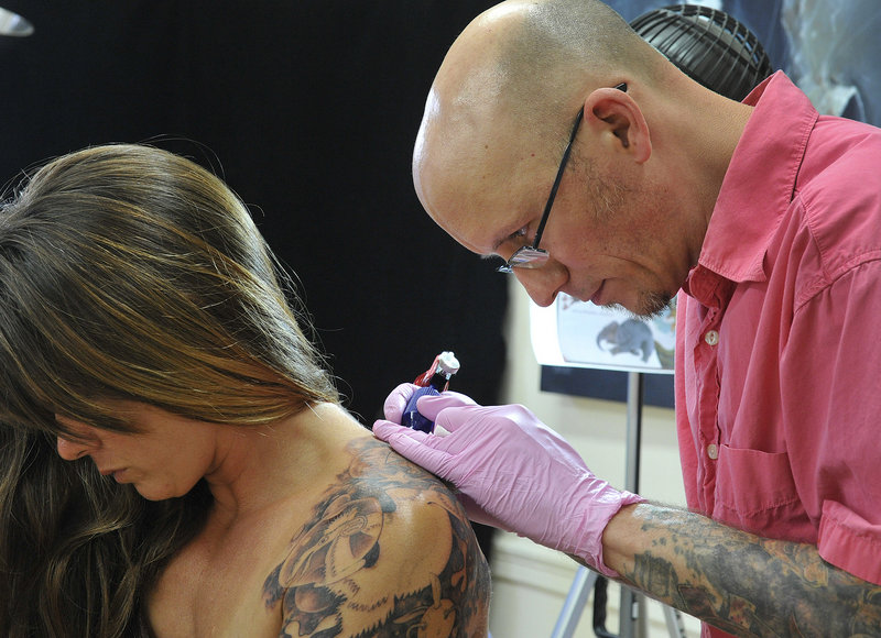"Chris Dingwell of Chris Dingwell Studio in Portland is part of the new wave of tattoo practitioners, college-educated businessmen with detailed professional portfolios. Dingwell, shown working with Jen Parker of Brattleboro, Vt., considers himself a tattoo ""artist."""