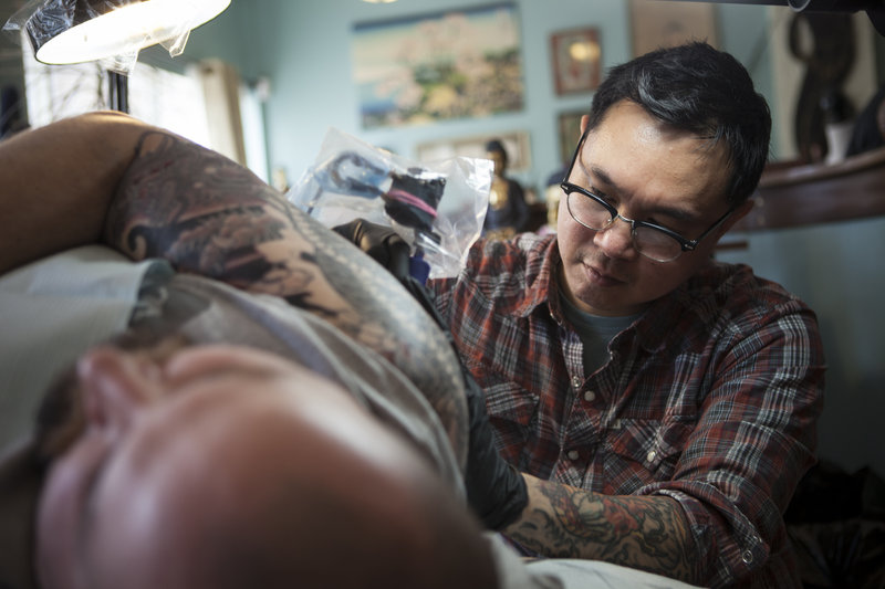 Phuc Tran works with a customer at his Tsunami Tattoo.
