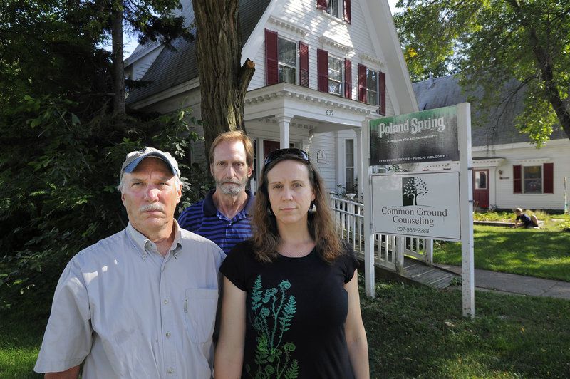 Fryeburg residents Bruce Taylor, left, an intervenor in the case, stands with contract opponents Cliff Hall and Nickie Sekera in front of the Poland Spring offices on Main Street in Fryeburg.