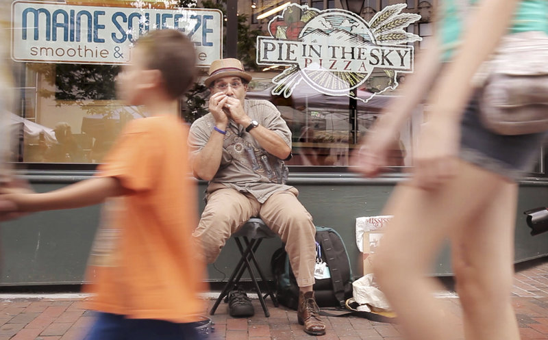Myron Samuels plays his harmonica in Portland's Monument Square during a farmers market on July 31.