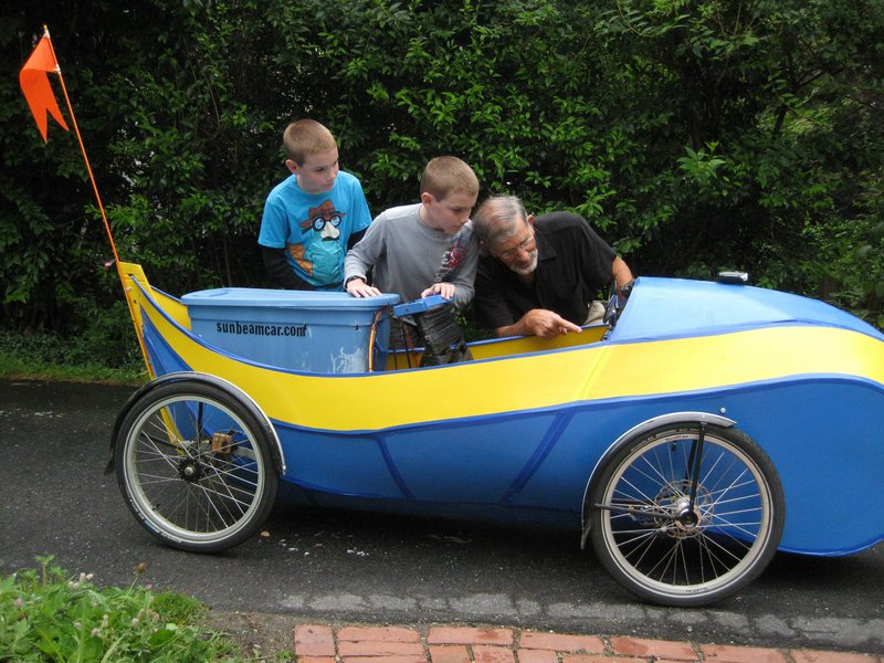 "Jory Squibb of Camden demonstrates his ""hybrid"" electric quadricycle to Daniel and Ethan Navarro of Rockland. Squibb will be one of the makers exhibiting his ""tinkering results"" at the Maker Faire on Saturday at the Camden Public Library. His 105-pound Sunbeam car is two-thirds battery-powered and one-third pedal-powered. The range on battery power alone is 80 miles. Midcoast Maine's Mini Maker Faire, the Greatest Show (and Tell) on Earth, is free and open to all ages. It will run from 11 a.m. to 3 p.m. in the library amphitheater."