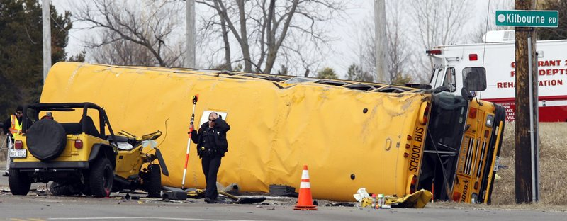 A Lake County, Ill., Sheriff's Police investigator examines a vehicle involved, April 5, in an accident with a school bus.