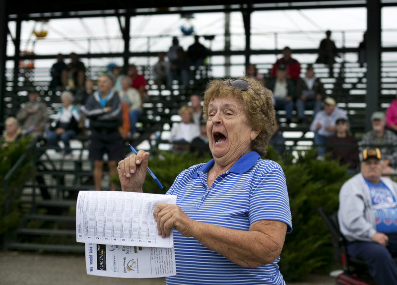 Sue Christiansen of Auburn cheers for a horse at the Windsor Fair on Thursday. Despite challenges, harness racing perseveres at many fairs and two tracks in Maine.