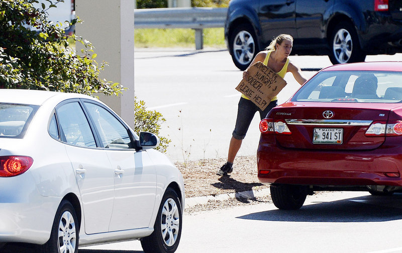 "A woman accepts money from a motorist Friday while panhandling from a median on Route 111 in Biddeford. Her sign reads: ""Homeless, hungry, & sober ... Please help!"""