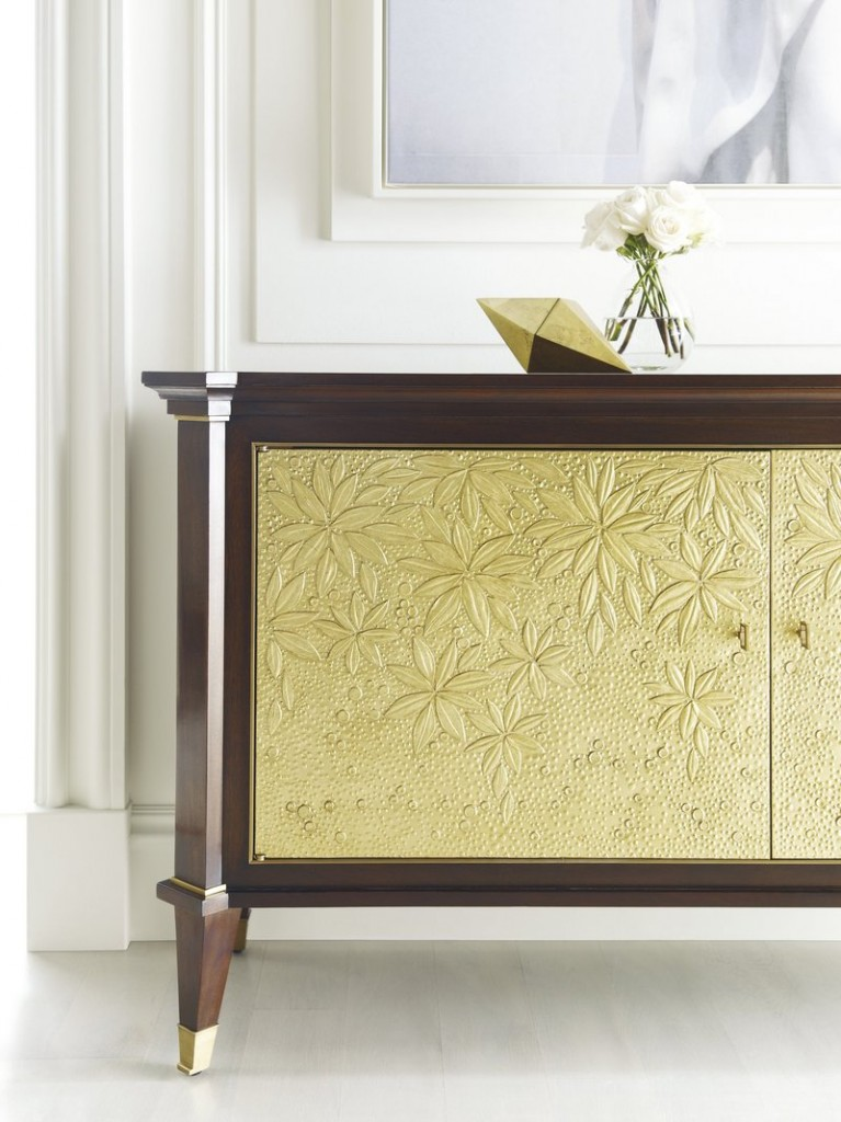 The doors of Baker Furniture's St. Honore Chest have a detailed design and gold finish that add drama.
