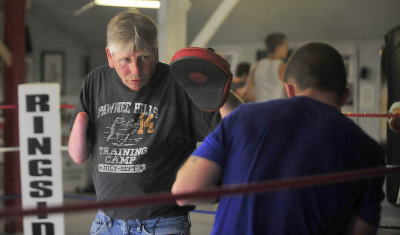 Skeet Wyman works with Brandon Berry to prepare him for the 12th annual Fight to Educate on Thursday.