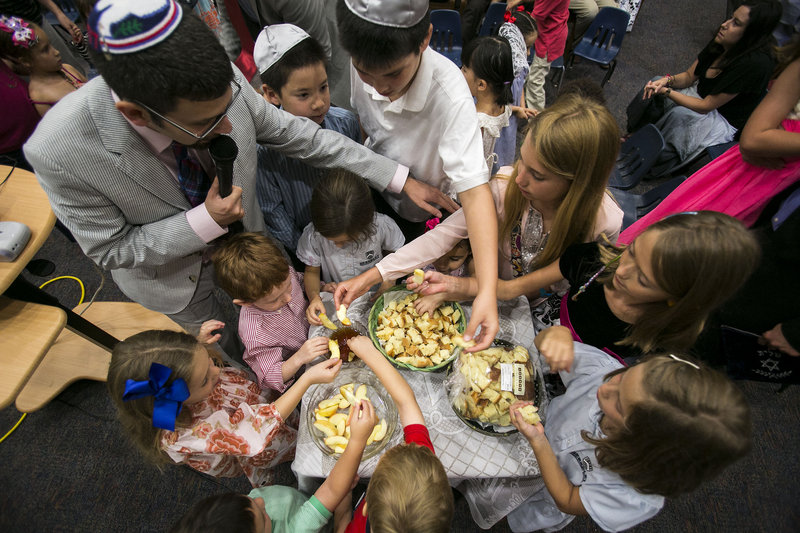 Rabbi Joshua Hearshen blesses children dipping apples into honey Wednesday during the Erev Rosh Hashana, the eve of the Jewish New Year service, at Congregation Rodeph Sholom in St. Petersburg, Fla. Dipping apples into honey is a tradition to bring a sweet new year.