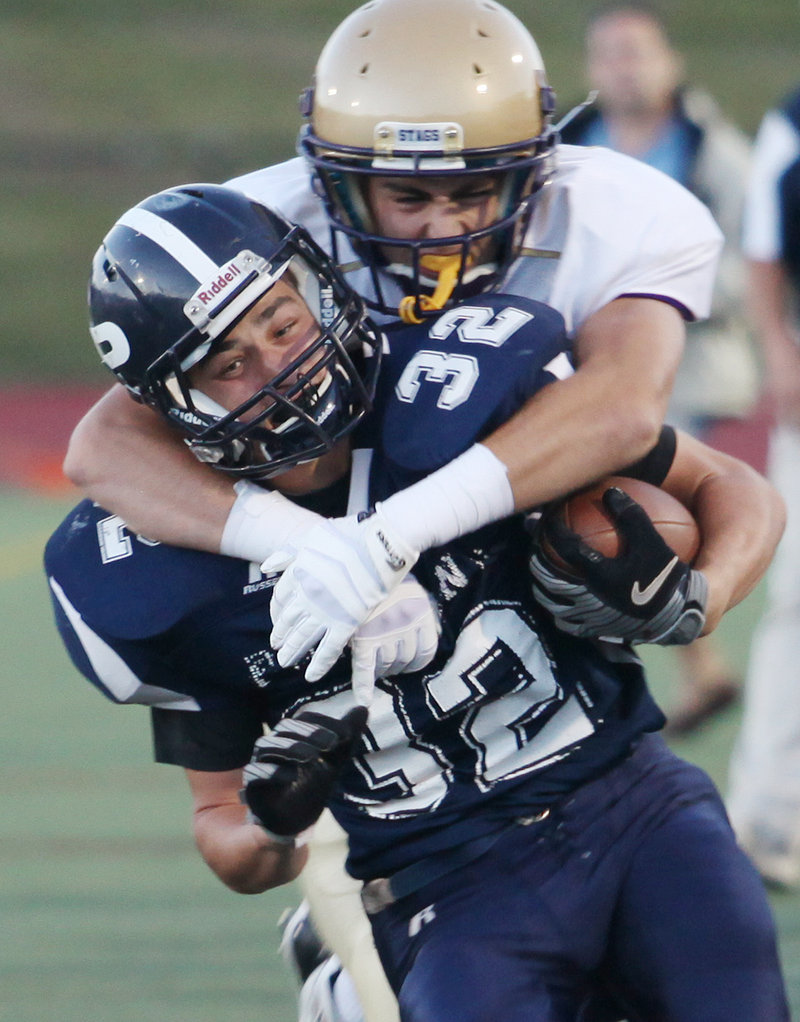 Sam Cross of Cheverus has a firm hold on Justin Zukowski of Portland during Cheverus' 35-25 victory Friday in an opener at Fitzpatrick Stadium.