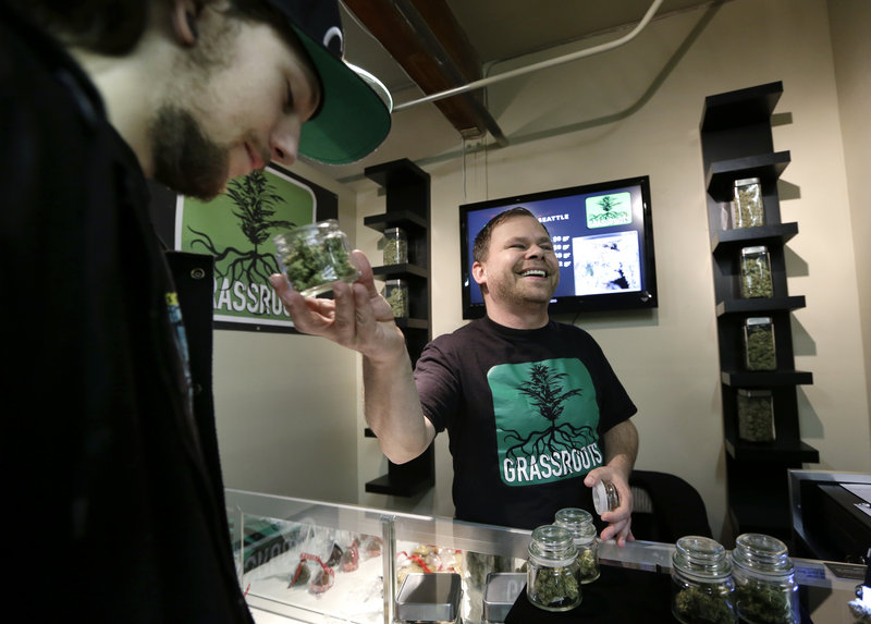 Vendor Jeff Simmons, right, smiles as he holds up a jar of marijuana for Dylan Tracy to sniff during the grand opening of the Seattle location of the Northwest Cannabis Market for sales of medical marijuana products on Feb. 13.