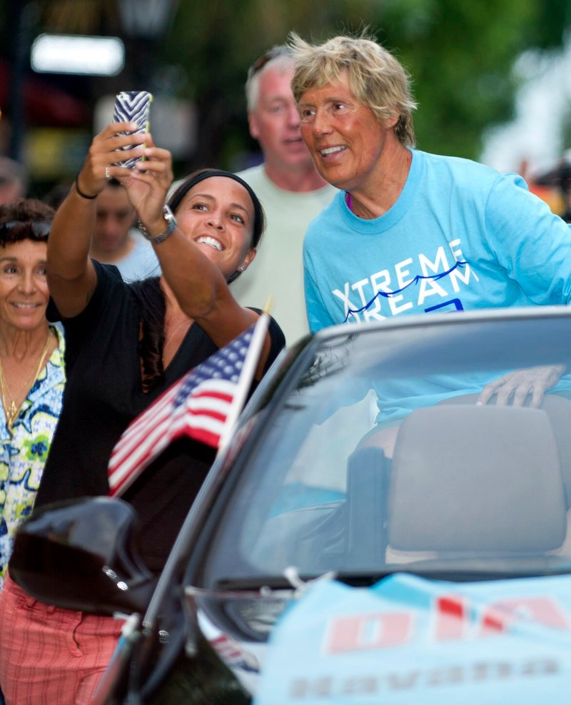 Diana Nyad views a fan's photo Tuesday during a parade in Key West, Fla.
