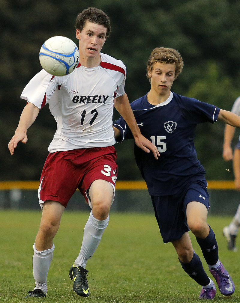 Greely's Samuel Porter keeps his eye on the ball as he tries to advance it up the field against Yarmouth's David Clemmer.
