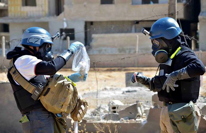 Members of a U.N. team take samples from sand to test for chemical weapons use in Syria. Russia's proposal to place Syria's chemical weapons stockpile under international control for dismantling would involve a complicated process.