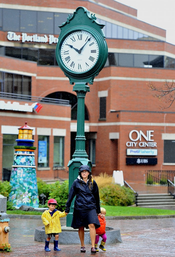 Laura Marston of Portland walks past the refurbished clock in City Center Plaza with her two children, Jack, 4, and Qunn, 2, after it was reinstalled Friday, Sept. 13, 2013.