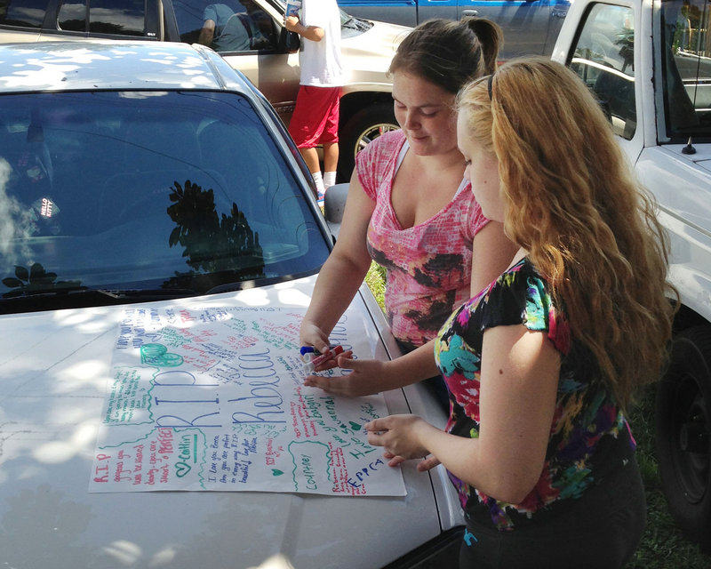 Summer Howard and Alecia Wilkins make a poster Tuesday for Howard's sister Rebecca Sedwick, 12, who jumped to her death Monday from a concrete plant's tower in Lakeland, Fla.