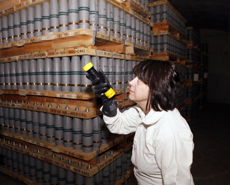 Debra Michaels, chemical operations manager of the Pueblo Army Chemical Storage facility in Pueblo, Colo., uses a flashlight to inspect mustard agent shells in one of the bunkers in 2010.