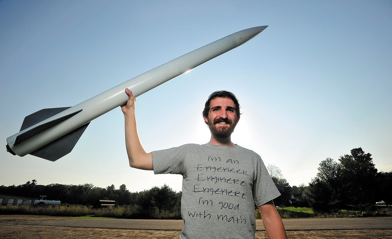 Mike Ostromecky, 22, of Winslow and six colleagues plan to launch an 18-foot, 500-pound rocket nearly 35 miles into the atmosphere this week. He designed the 5-foot rocket he is holding, which reached 2,000 feet.