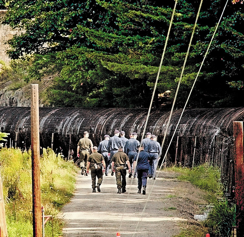 Game wardens and police academy cadets walk toward the scene in Oakland a day after Colby College senior Dawn Rossignol's body was found.