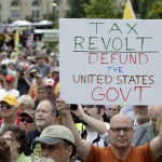 """A man holds up a placard during a Tea Party rally to """"Audit the IRS"""" in front of the U.S. Capitol in Washington"""