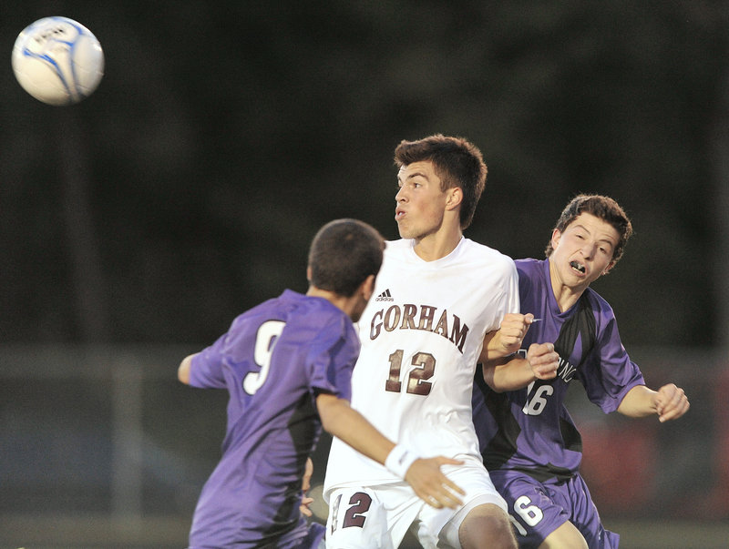 Corey Nadeau of Gorham heads the ball away from Ahmed Adnan, left, and Isaac Santerre of Deering during an early-season game between undefeated SMAA boys' soccer teams Tuesday night. Gorham pressured for much of the game but Deering's early goal stood up for a 1-0 win.