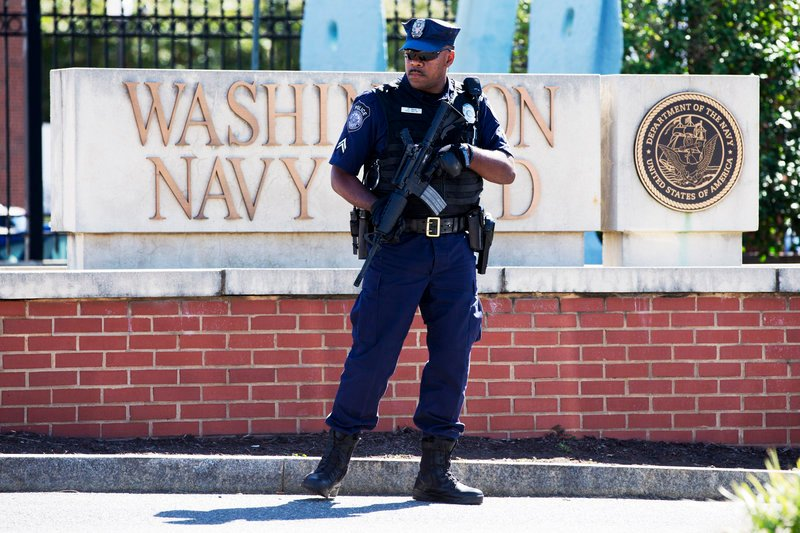 An armed officer who said he is with the Department of Defense, works near the gate at the Washington Navy Yard in Washington, D.C., on Tuesday, a day after a gunman launched an attack there.