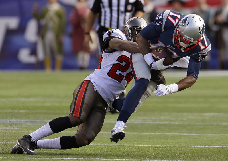 Patriots rookie Aaron Dobson is brought down by Tampa Bay's Darrelle Revis after one of his seven receptions Sunday.