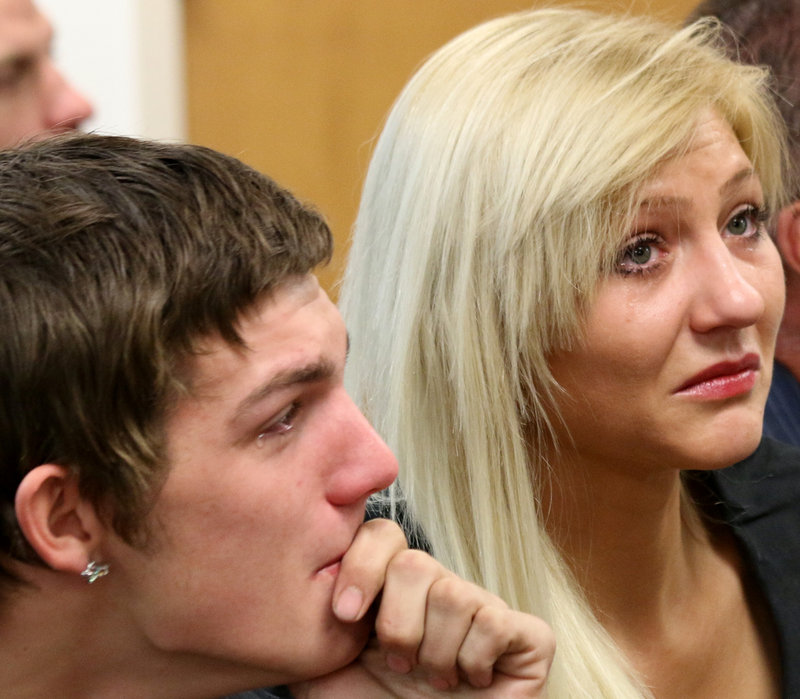 Scott Martin, Darriean Hess' fiancé, left, and Cassandra Clifton, Hess' sister, watch a video screen as Darriean Hess, is arraigned via video in Seabrook, N.H. Wednesday, Sept. 25, 2013. Darriean Hess is charged with two counts of negligent homicide and two counts of assault after she plowed into a group of cyclists on Saturday on a bridge during an annual ride in Hampton. Two riders died and two were injured.