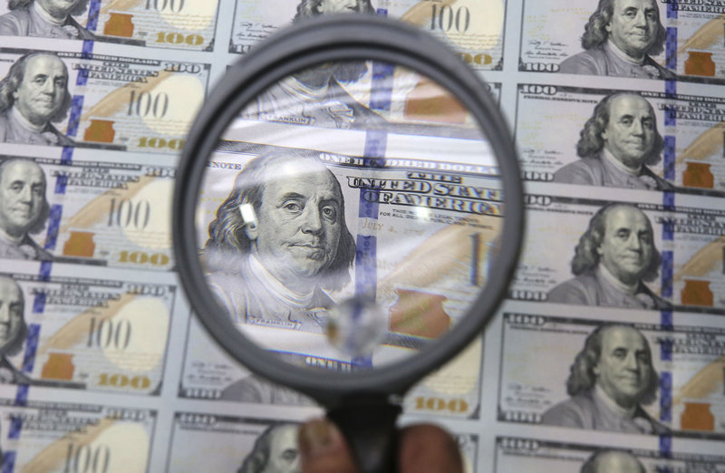A sheet of uncut $100s gets a quick inspection at the Bureau of Engraving and Printing Western Currency Facility in Fort Worth, Texas, on Tuesday.